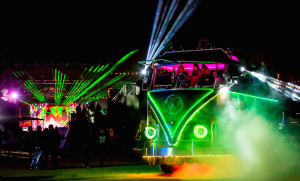 night time burning man scene with a neon VW bus , lasers, and dancers
